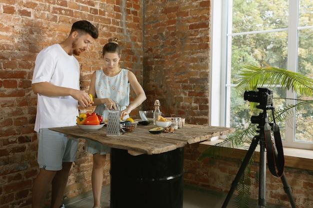 Giovane coppia che cucina e registra video dal vivo per vlog e social media