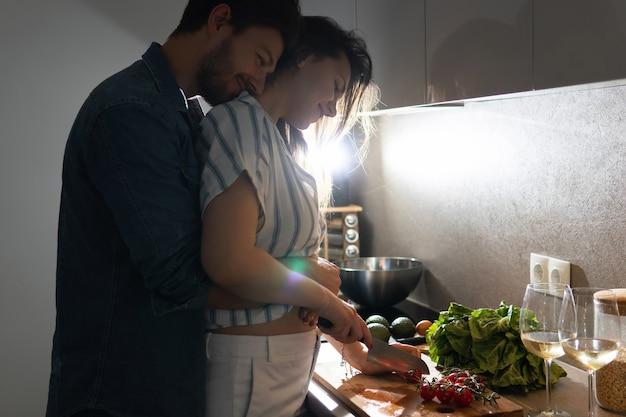 저녁에 부엌에서 함께 맛있는 저녁 식사를 요리하는 젊은 부부