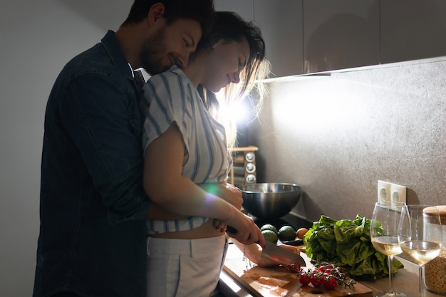 Young couple cooking tasty dinner together in a kitchen at evening