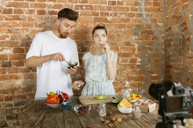 Молодая пара вместе готовит и записывает живое видео для видеоблога