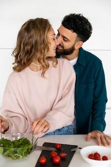 家で一緒に料理をする若いカップル