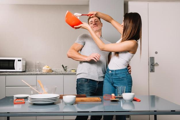 Молодая пара приготовления пищи вместе в кухне