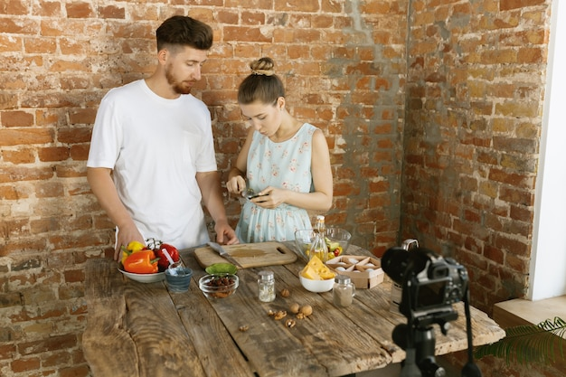 Young couple cooking together and recording live video for vlog