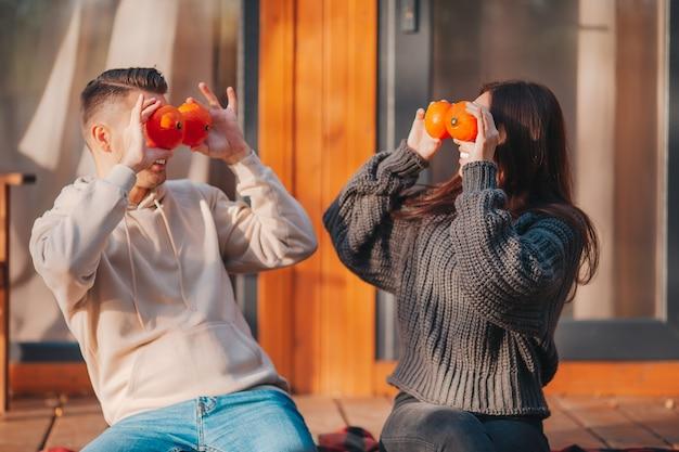 젊은 부부는 그들의 집 테라스에서 가을 따뜻한 날에 호박으로 눈을 가렸다.
