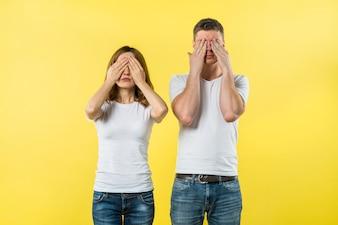 Молодая пара закрыла глаза на желтом фоне