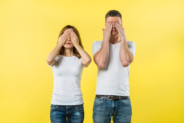 Young couple covering their eyes against yellow background