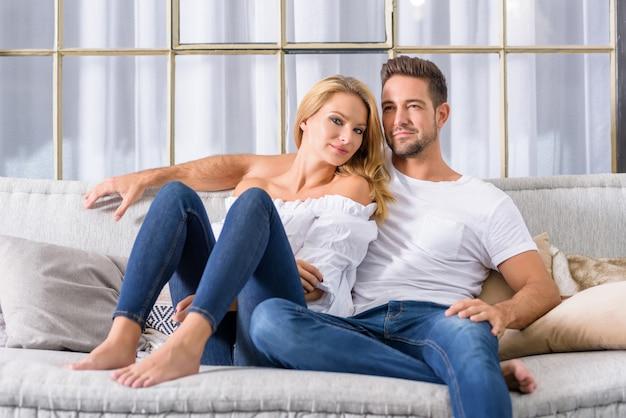 ソファに寄り添う若いカップル