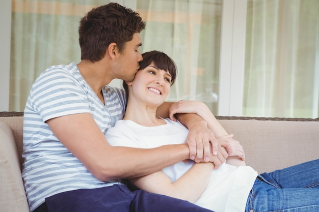 Young couple cuddling on sofa in living room