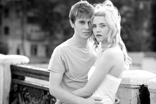 日当たりの良い晴れた夏の日の橋を歩きながら抱きしめる若いカップル。愛とロマンスと忠実さの概念