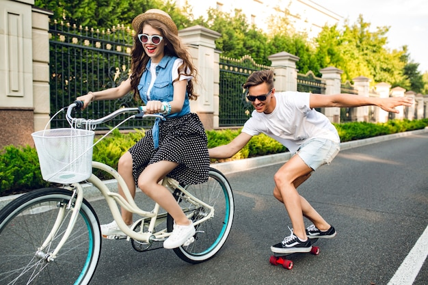 Young couple of cute teenagers  having fun on summer on sunset on road. pretty girl with long curly hair in hat driving a bike, handsome guy keeps bike and rides on a skateboard.