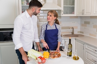 Young couple cutting pizza in kitchen
