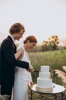 Молодая пара разрезает свадебный торт