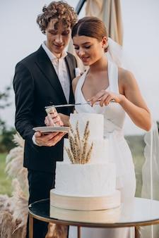 ウエディングケーキを切る若いカップル