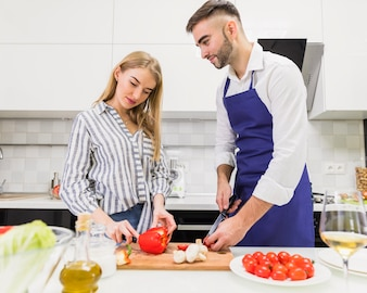 Young couple cutting vegetables for salad on board