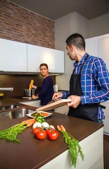 食べ物を準備するために台所で野菜を切る若いカップル