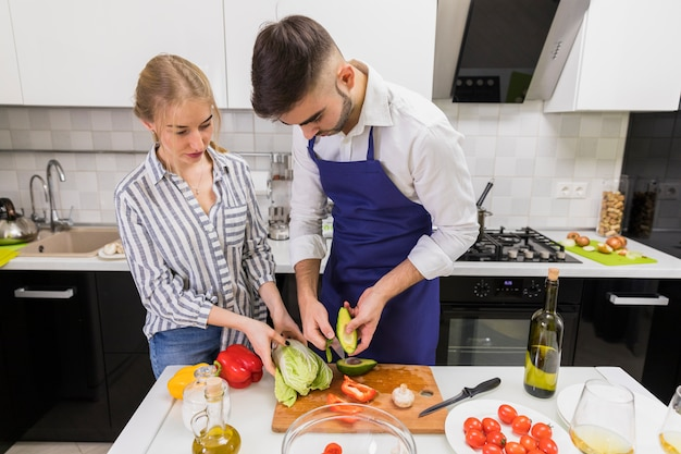 Young couple cutting vegetables on wooden board