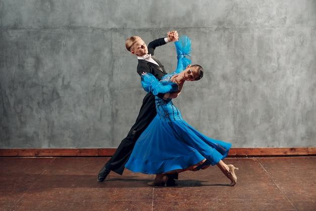 Молодая пара танцует медленный вальс в бальном зале.