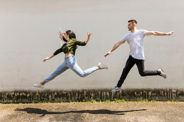 Young couple dancer jumping in front of wall