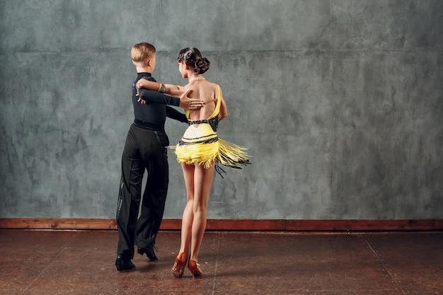 Молодая пара танцоров танцует бальные танцы ча-ча-ча.