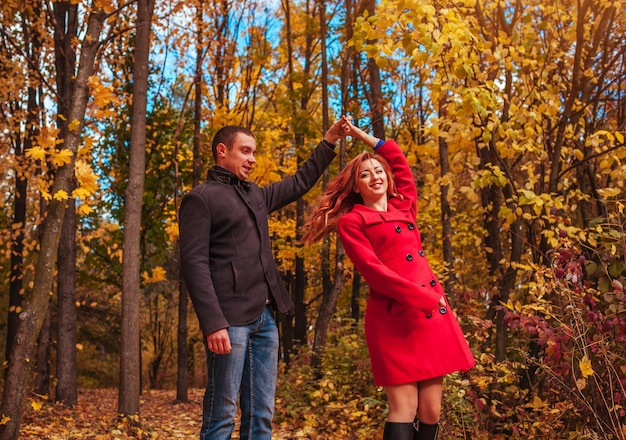 Young couple dances in autumn forest among colorful trees