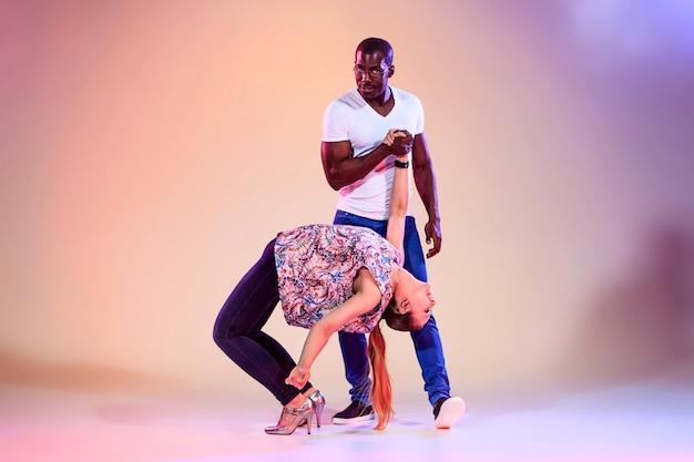 젊은 부부는 사교적인 카리브 살사 춤을 추고, 스튜디오는 라일락 배경에서 촬영합니다. 긍정적인 인간의 감정. 흑인 아프리카 및 백인 모델