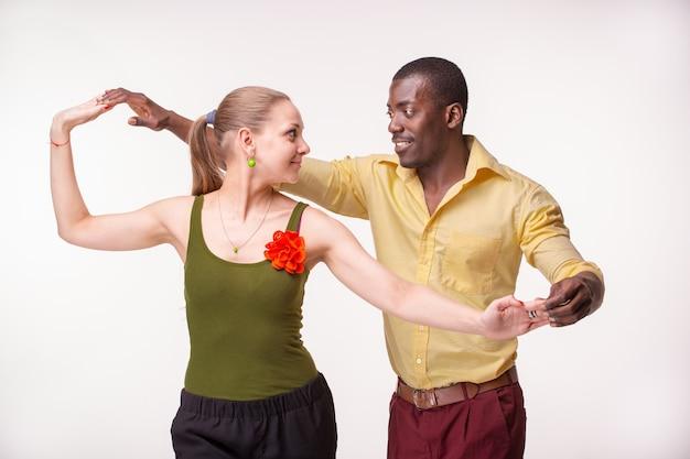 젊은 부부는 사교적인 카리브 살사 춤을 추고, 스튜디오는 흰색 배경에서 촬영됩니다. 긍정적인 인간의 감정. 흑인과 백인 모델