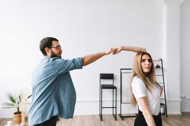 新しいアパートの明るいリビングルームで踊る若いカップル。