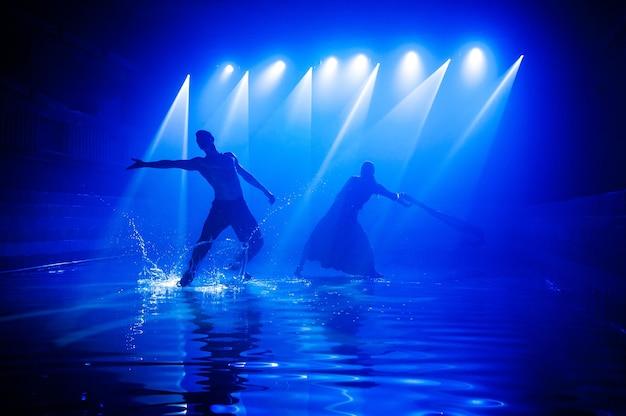 Молодая пара танцует в воде.