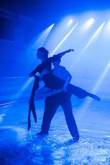 Молодая пара танцует в воде
