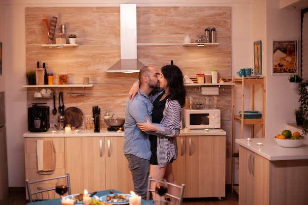 Giovane coppia che balla in cucina durante una cena romantica