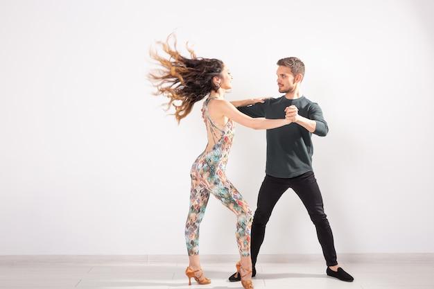 라틴 댄스 바차타, 메렝게, 살사, 키좀바를 춤추는 젊은 부부. 복사 공간이 있는 흰색 배경 위에 두 개의 우아한 포즈
