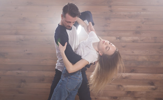 라틴 댄스 바차타, 메렝게, 살사, 키좀바를 춤추는 젊은 부부. 흰색 배경 위에 두 우아함 포즈입니다.