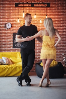 Young couple dancing latin music: bachata, merengue, salsa. two elegance pose on cafe with brick walls