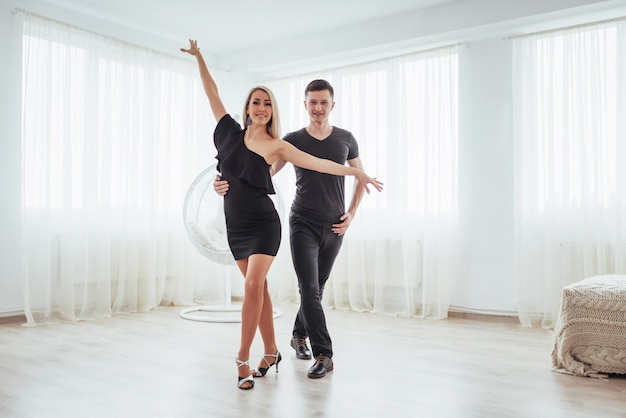 Young couple dancing latin music: bachata, merengue, salsa. two elegance pose on white room