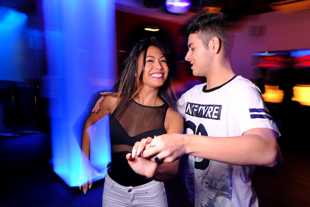 A young couple dancing salsa and bachata at a night club