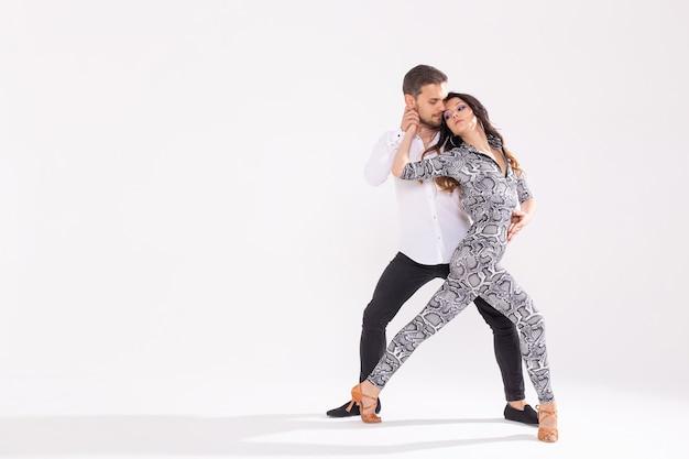 사회 라틴 댄스 바차타, 메렝게, 살사 춤을 추는 젊은 부부. 복사 공간이 있는 흰색 배경에 두 개의 우아한 포즈