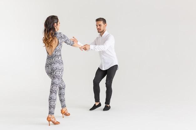Молодая пара танцует социальный латинский танец бачата, меренге, сальса. две элегантные позы на белой стене.