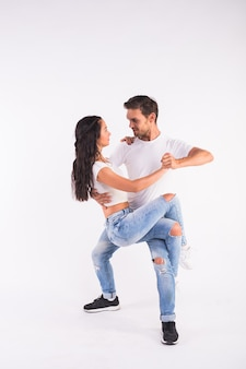 Young couple dancing social latin dance bachata, merengue, salsa. two elegance pose on white wall.