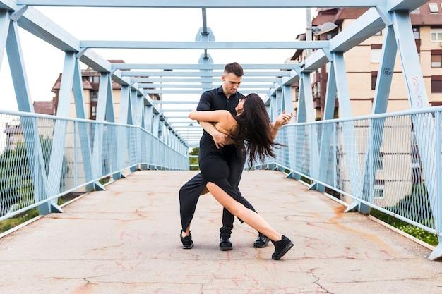 Young couple dancing tango over the bridge