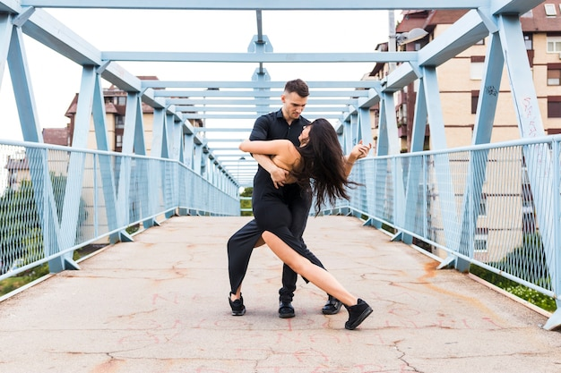 Молодая пара танцует танго над мостом