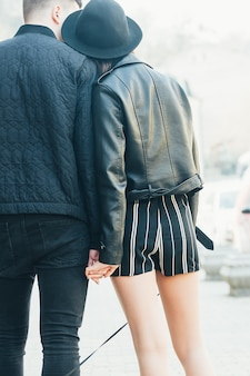 Young couple on date holding hands back view