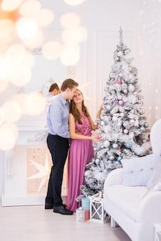 若いカップルがクリスマスツリーを飾ります。クリスマスの部屋の男性と女性のクリスマスのための派手な服。