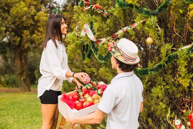 若いカップルがクリスマスツリーを飾ります。公園のクリスマスツリーで幸せなカップル。