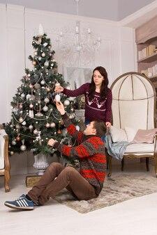 装飾や装飾品をぶら下げて自宅のリビングルームでクリスマスツリーを飾る若いカップル