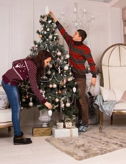 リビングルームのインテリアに伝統的な緑のクリスマスツリーを飾る若いカップルは、装飾をぶら下げ、上に飾りを置くためにストレッチします