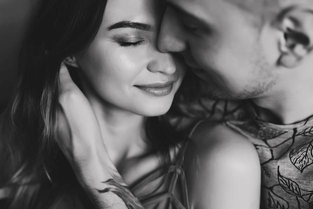 Молодая пара глубоко влюблена, обниматься и целоваться. день святого валентина, любовь, романтика, концепция семьи. черно-белое фото