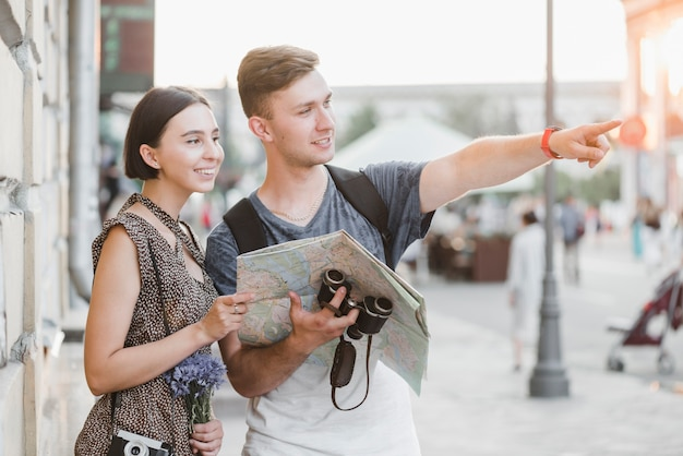 Young couple discovering city with map