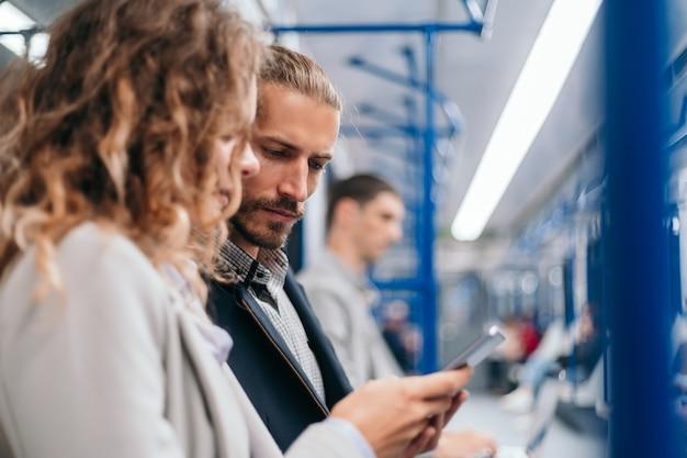 지하철 차량에서 온라인 뉴스를 논의하는 젊은 부부