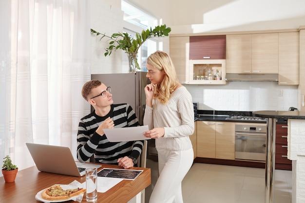 Молодая пара обсуждает печатные документы с программным кодом, оставаясь дома и работая над новым мобильным приложением