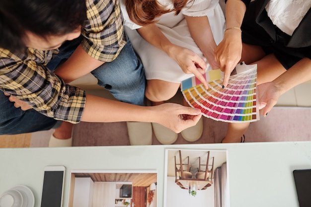 Young couple discussing wall color in new apartment with interior designer, top view